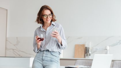 Portrait of a happy attractive woman using mobile phone while holding cup of tea and leaning on a table with laptop computer at home